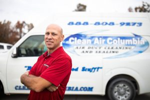 Clean Air Columbia professional air quality technician standing next to service van.
